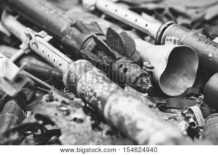 remnants of shells anti-tank rocket propelled grenade launcher and High Mobility Artillery Rocket System black and white photo