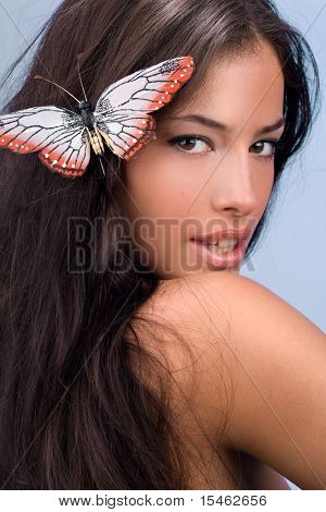 female portrait with butterfly in hair, studio shot