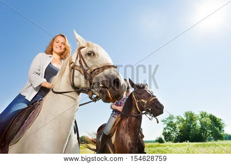 Close-up portrait of two happy female equestrians riding beautiful purebred horses at flowery meadows