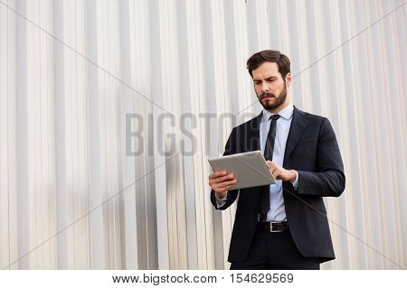 Elegant Businessman  Using A Tablet Outside