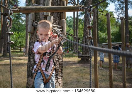 kid having a quest in the rope park. climing throgh rope bridge.
