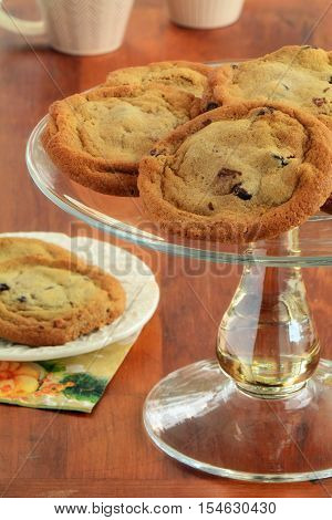 Fresh baked chocolate chip cookies on glass cake stand with two cookies on a plate. Horizontal format. Warm wood table with two mugs in background. Macro with shallow depth of field. Focus on front cookie.