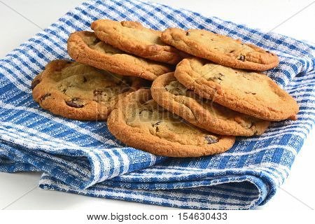 Fresh baked chocolate chip cookies on blue and white tea towel in horizontal format. Macro with shallow depth of field.