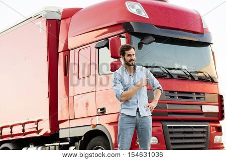 Masculine Truck Driver In Jeans With His Truck Behind