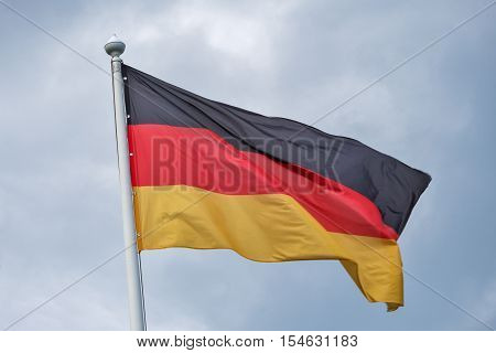 The flag of Germany flutters on wind against the background of gray clouds.