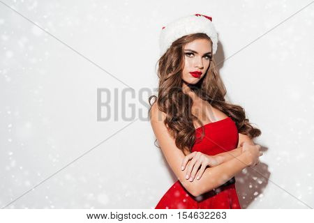 Beautiful brunette woman in red dress and hat with hands crossed isolated over white background