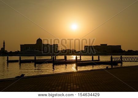 SHARJAH, UAE - OCTOBER 10, 2016: A sunset silhouette of Government buildings against the fishing port