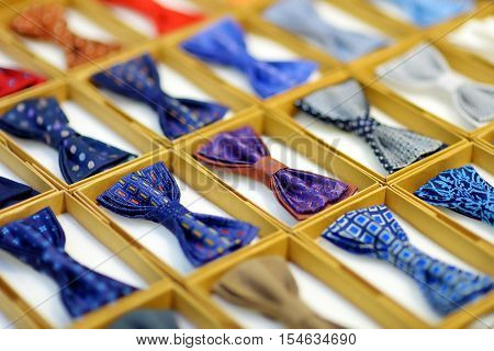 Rows of colorful bow-ties in boxes on wedding fair