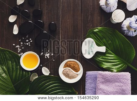 Spa treatment tools and aromatherapy concept background. Zen stones, aroma salt, spices, herbal balls and oil, details of wellness body care and alternative indian medicine, top view