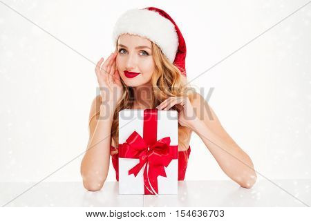 Portrait of smiling beautiful young woman in santa claus costume with gift box over white background