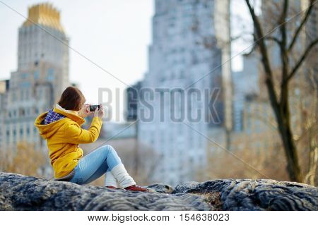 Beautiful Young Woman Taking A Photo Of Skyscapers