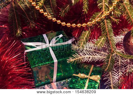 Green gift box under Christmas tree branches. Wrapped in green paper gift box Toned image