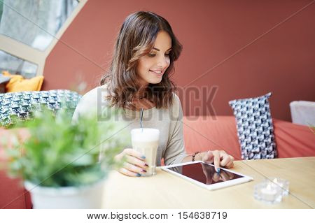 Young Woman Using Tablet At Cafe