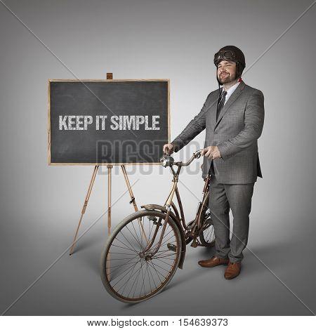 Keep it simple text on blackboard with businessman and vintage bike