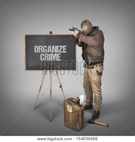 Organize crime text on blackboard with man holding machine gun