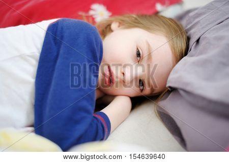 Little preschooler girl in bed on sunny morning