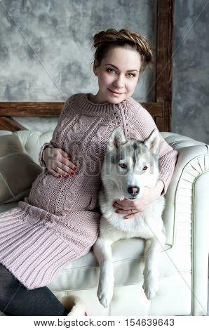 Young beautiful pregnant woman huging husky dog on the sofa