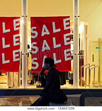 LIVERPOOL UK 31st OCTOBER 2016. A man sitting outside a shop with a sale sign at night