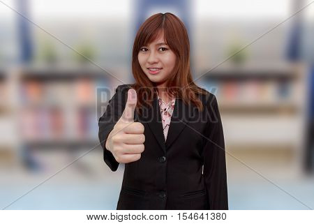 Smiling businesswoman holding thumps up in front of book shelf - feel good business concept.