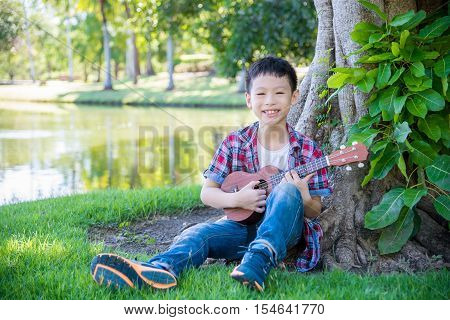 Young asian boy playing ukulele in park