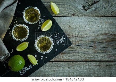 Gold tequila with lime and salt on rustic wood background