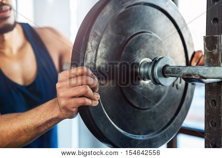 Cropped image of a bodybuilder guy with barbell in a gym, keep barbell plate in hands