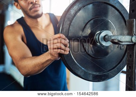 Cropped image of a healthy fit guy with barbell in a gym, keep barbell plate in hands