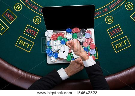 casino, online gambling, technology and people concept - close up of poker player with playing cards, laptop and chips at green casino table. top view. in the hands of two aces, a winning combination poster