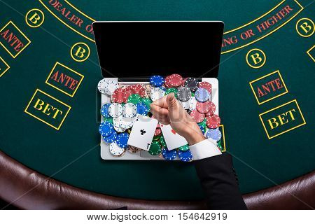casino, online gambling, technology and people concept - close up of poker player with playing cards, laptop and chips at green casino table. top view. in the hands of two aces, a winning combination