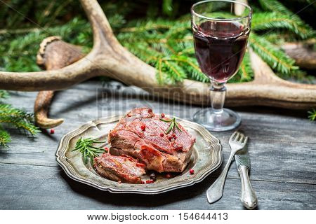Red wine in a glass and venison on a plate