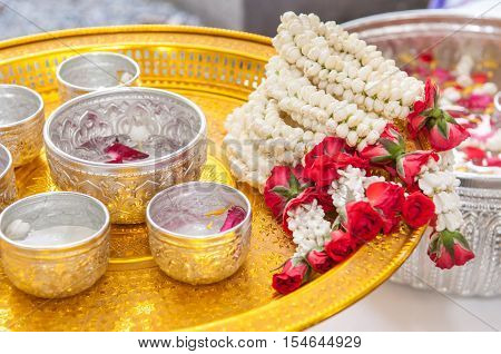 Thai garland Flowers and Water with jasmine and roses corolla in bowl on golden tray (Use for Songkran festival in Thailand)