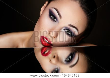 High fashion look.glamour fashion portrait of beautiful sexy brunette model with bright makeup and red lips and her reflection in mirror table on dark