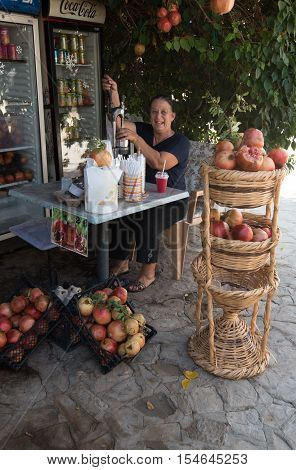 Famagusta Cyprus - September 15 2016: Senior woman making fresh healthy pomegranate juice with a fruit press machine.