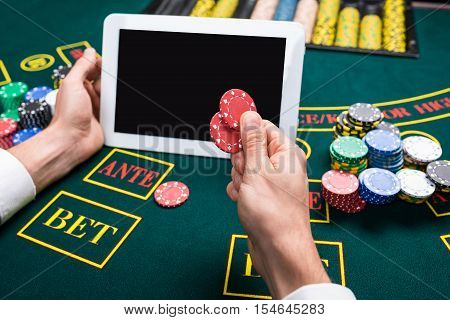 casino, online gambling, technology and people concept - close up of poker player with playing cards, tablet and chips at green casino table. first-person view. It makes chips bet