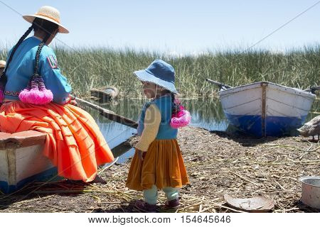 Aymara girl with her mother at the shoreside on one of the Uros Islands. October 16 2012 - Lake Titicaca Peru