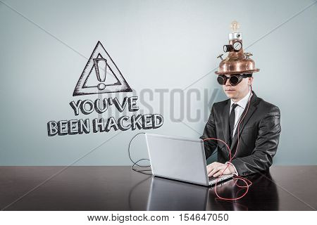 You have been hacked text with vintage businessman using laptop at office