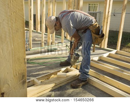 Hispanic man using a nail gun to frame a house on a construction site.