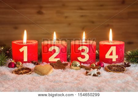 Four Advent Candles Lit In Snow