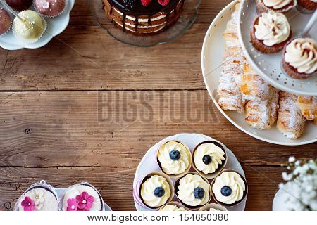 Table with cake, cupcakes, cakepops and horn pastries. Studio shot on brown wooden background. Copy space. Flat lay.
