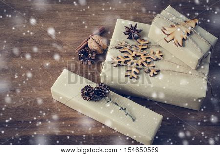 Vintage Kraft Boxes with Gifts Decorated with Wooden Snowflake Christmas Tree and Jute on Wooden Background. Snow Falling Effect. Rustic Style. View from above with copy space.