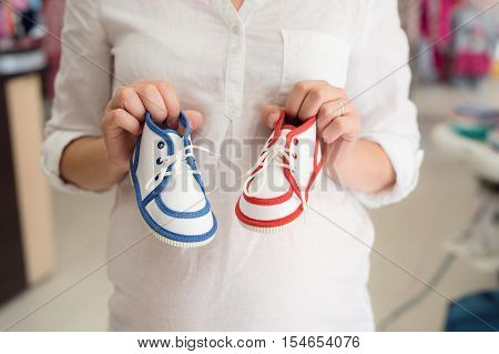 Unrecognizable pregnant woman in white shirt shopping shoes for her baby, not knowing whether to buy blue for boy or red for girl