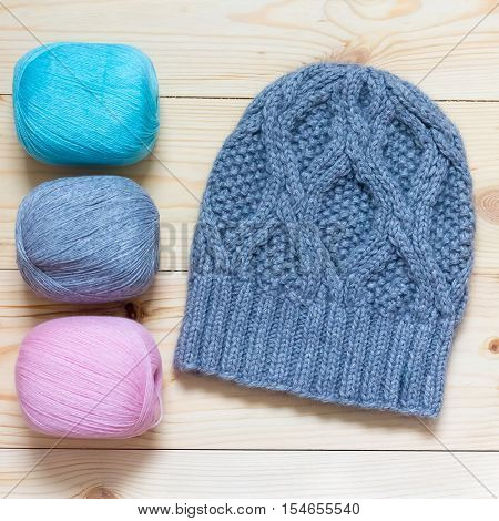 Gray-blue Hat Knitted By Hand On A Light Wooden Background And Three Skeins Of Wool