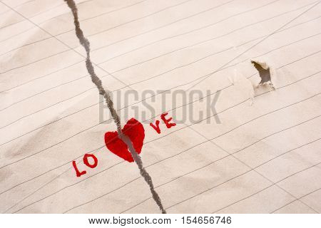 Torn paper with a heart shape says love