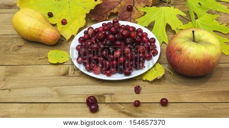 On a wooden surface lie autumn leaves with apple and pear and is white plate with cranberries.