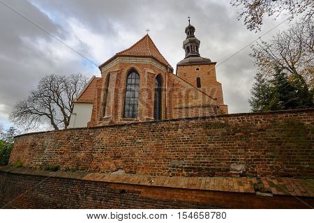 Brick medieval wall and the Gothic parish church in Gniezno