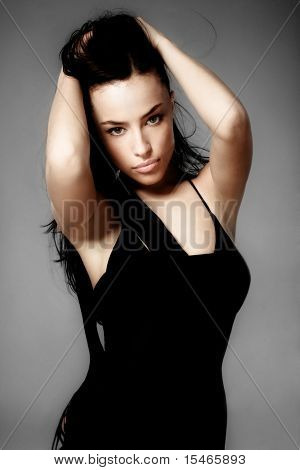 elegant beautiful dark haired woman with hands in hair