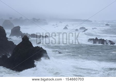 Dramatic waves crashing onto rocks and the rugged Northern California Coastline during a storm taken in Sonoma, CA