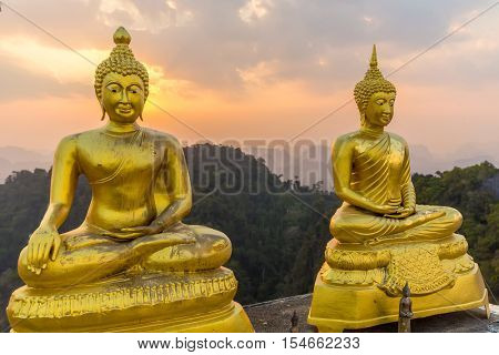 Two Buddha statue on the mountain top under the sunset, Krabi tiger cave temple, Thailand