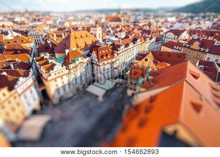 Top cityscape view on the old town square from the clock tower during the sunset in Prague. Blurred image with tilt-shift technic