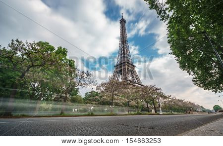 Perspective View of The Eiffel Tower in Paris against cloud sky and road with car trails, long exposure